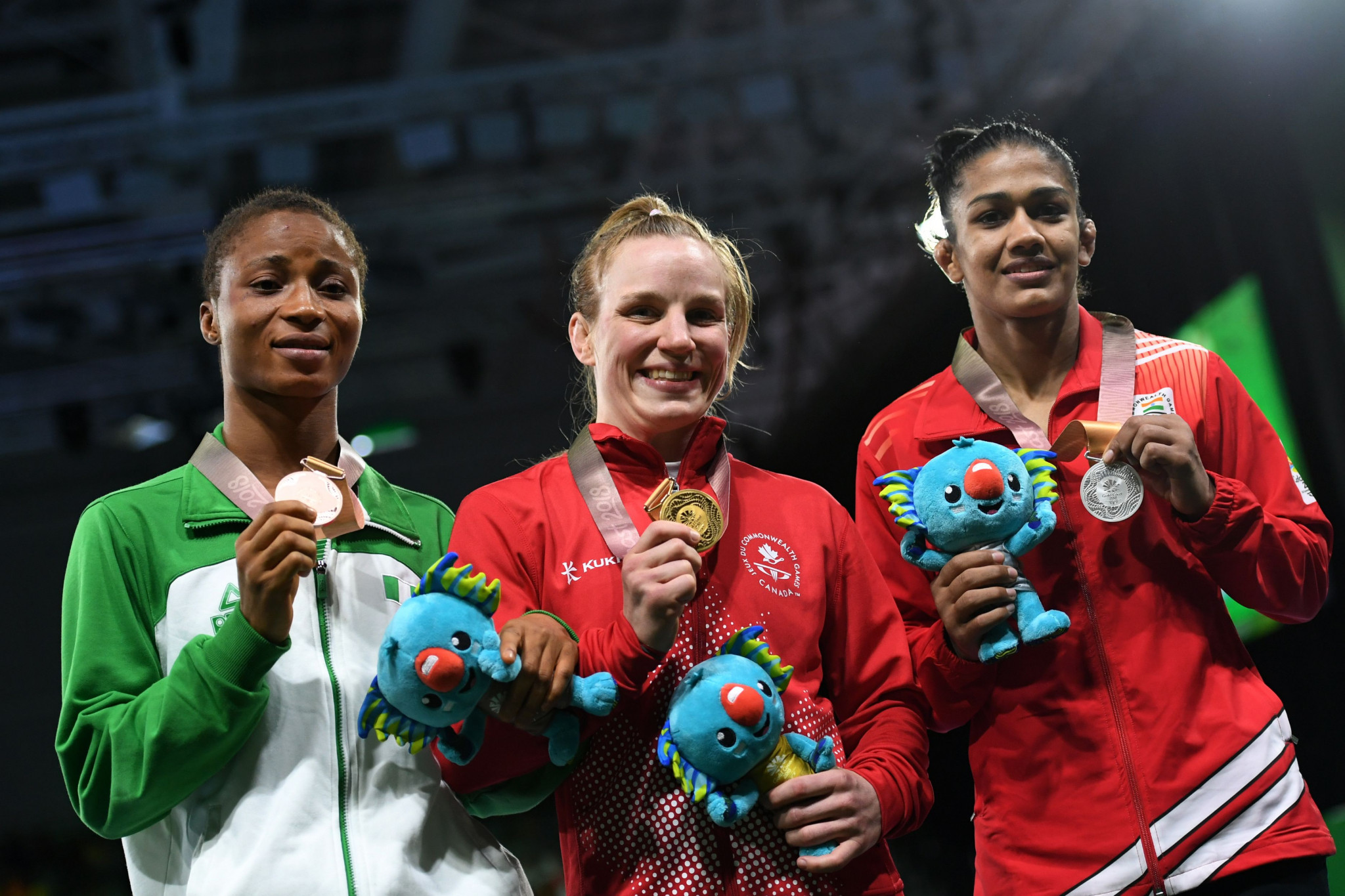Canada's Diana Weicker, centre, thanked her family and friends after winning the women's 53kg category ©Getty Images