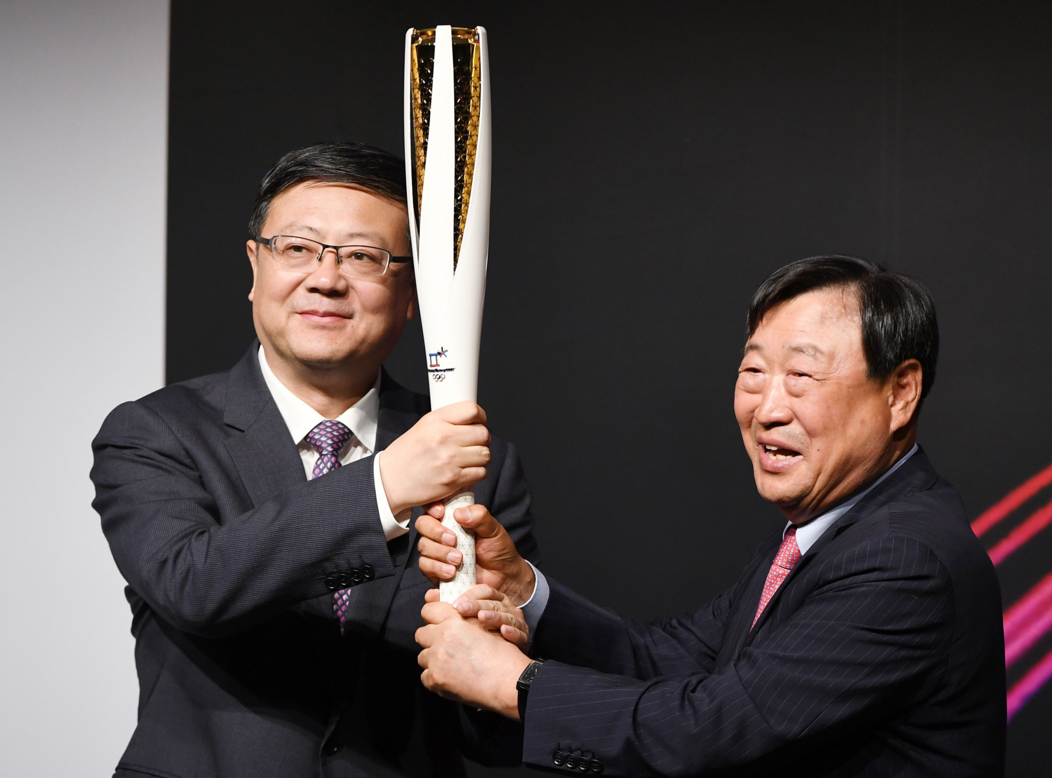 Pyeongchang 2018 President Lee Hee-beom, right, passes the Olympic Torch to Beijing Mayor Chen Jining ©Getty Images