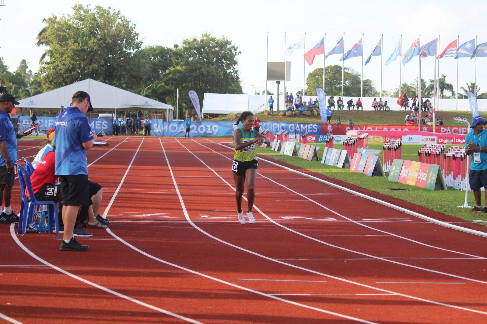 Women's 10,000m champion Sharon Kikini Firisua checks her time as she crosses the line ©Games News Service