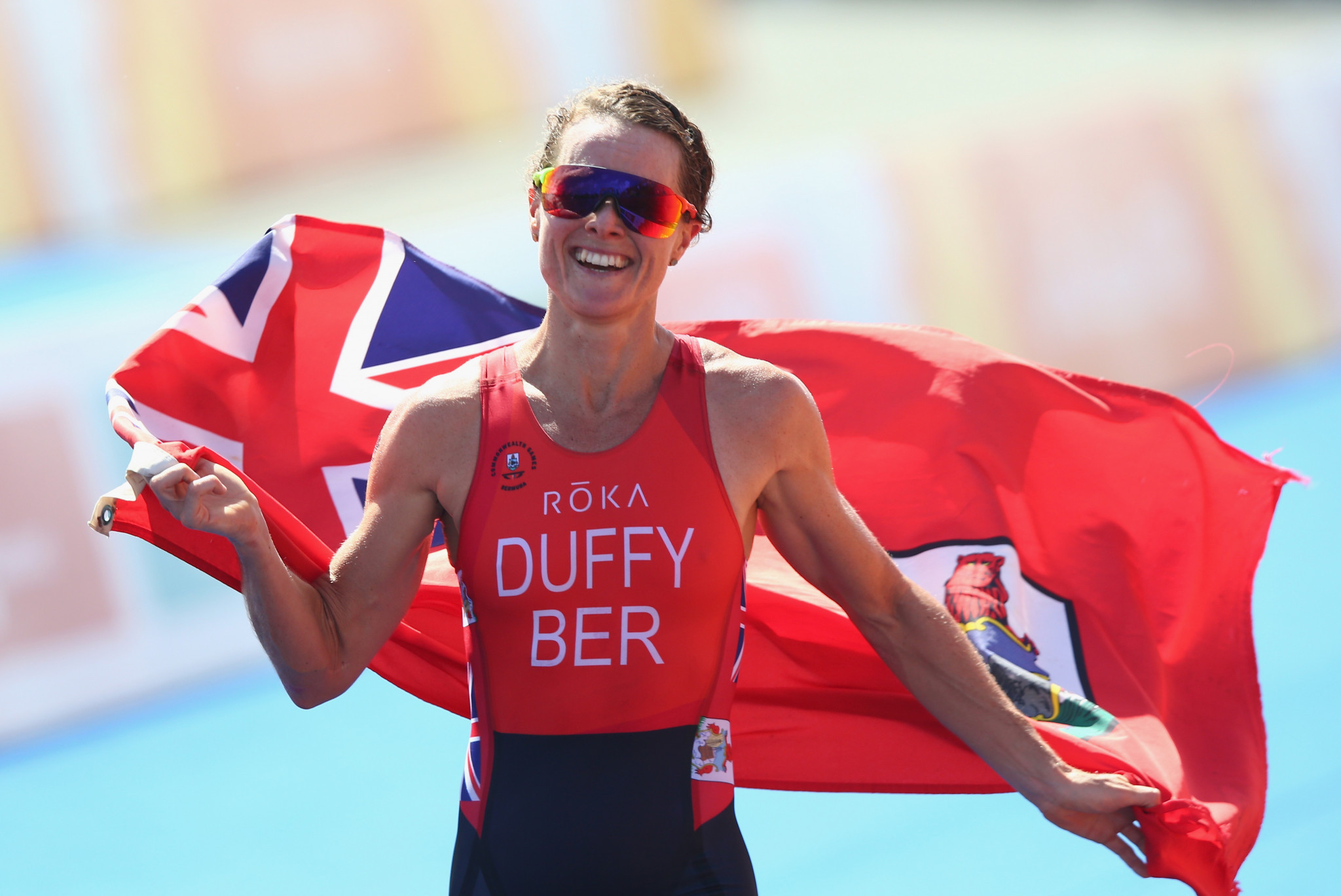 Flora Duffy of Bermuda celebrates on her way to winning gold during the Women's Triathlon on day one of the Gold Coast 2018 Commonwealth Games ©Getty Images