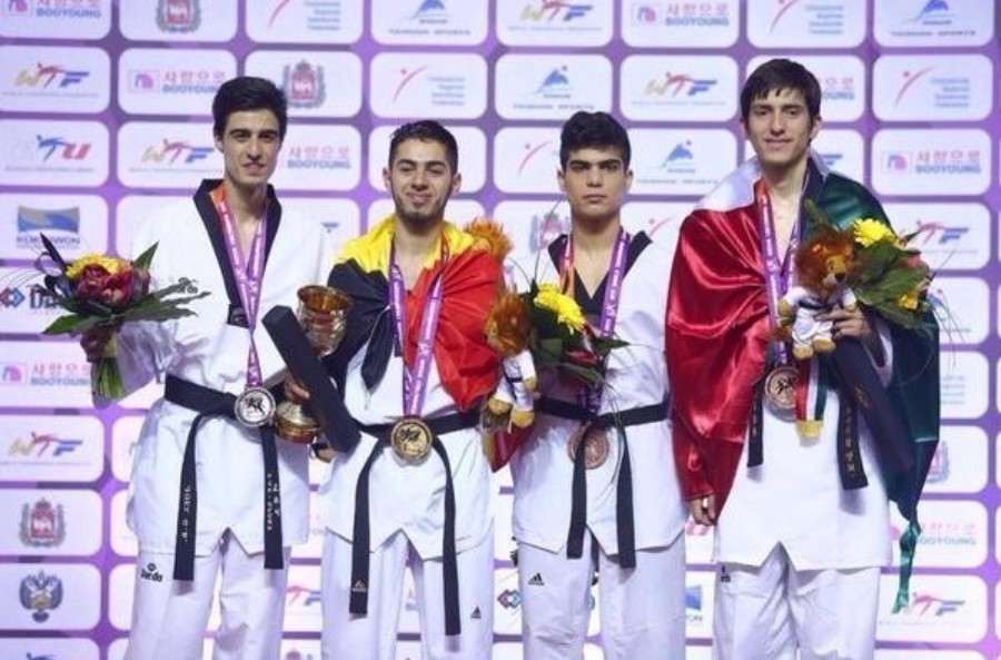 Jaouad Achab (second left) wrapped in the Belgium flag after winning World Championship gold in Chelyabinsk ©WTF