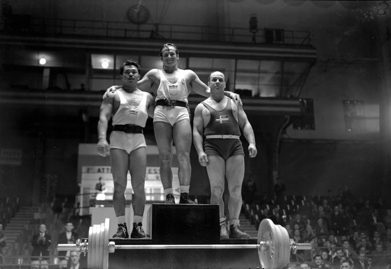 The three winners of the 1948 Olympic Light Heavyweight Weightlifting take their places on the podium in Earl's Court, London. The winner is Stanley Stanczyk of USA, in second place is Harold Sakata of USA and in third place came Klas Gosta Magnusson of Sweden. © PNA Rota/Getty Images.