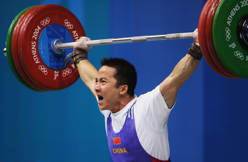 Zhiyong Shi of China competes in the men's 62 kg category weightlifting competition on August 16, 2004 during the Summer Olympic Games at Nikaia Olympic Weightlifting Hall in Athens, Greece. © Chris McGrath/Getty Images.