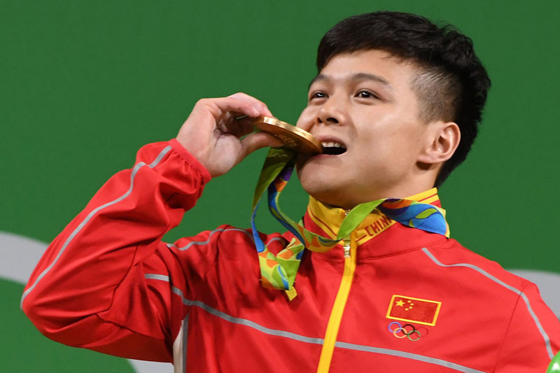 China's gold medallist Long Qingquan poses with his medal on the podium after the men's 56kg weightlifting event at the Rio 2016 Olympic games in Rio de Janeiro on August 7, 2016. © GOH CHAI HIN/AFP via Getty Images.
