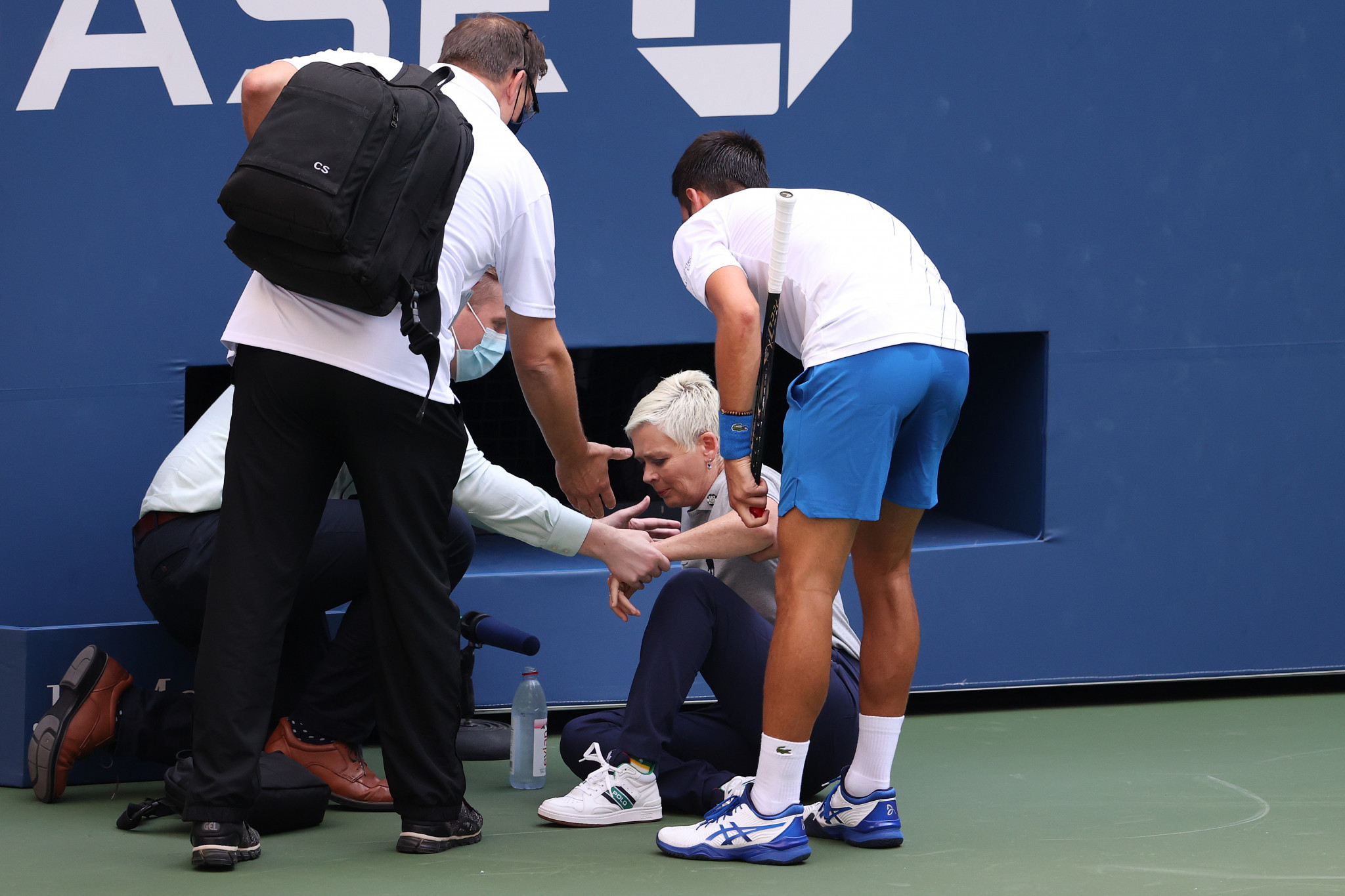 Novak Djokovic helps a line judge after he inadvertently struck her with a ball at the US Open ©Getty Images