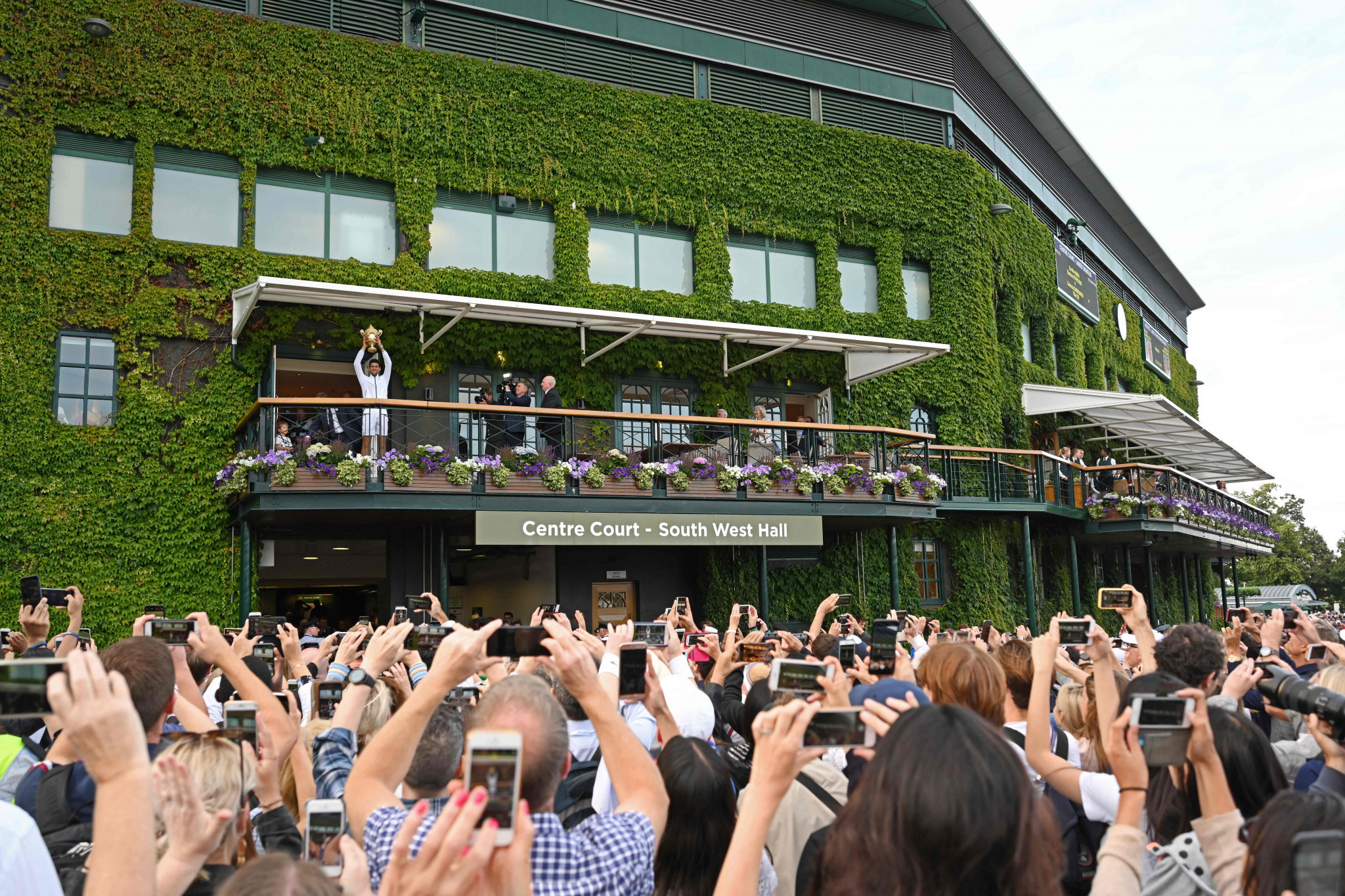 Fans take pictures of Novak Djokovic celebrating his men's singles victory at Wimbledon ©Getty Images