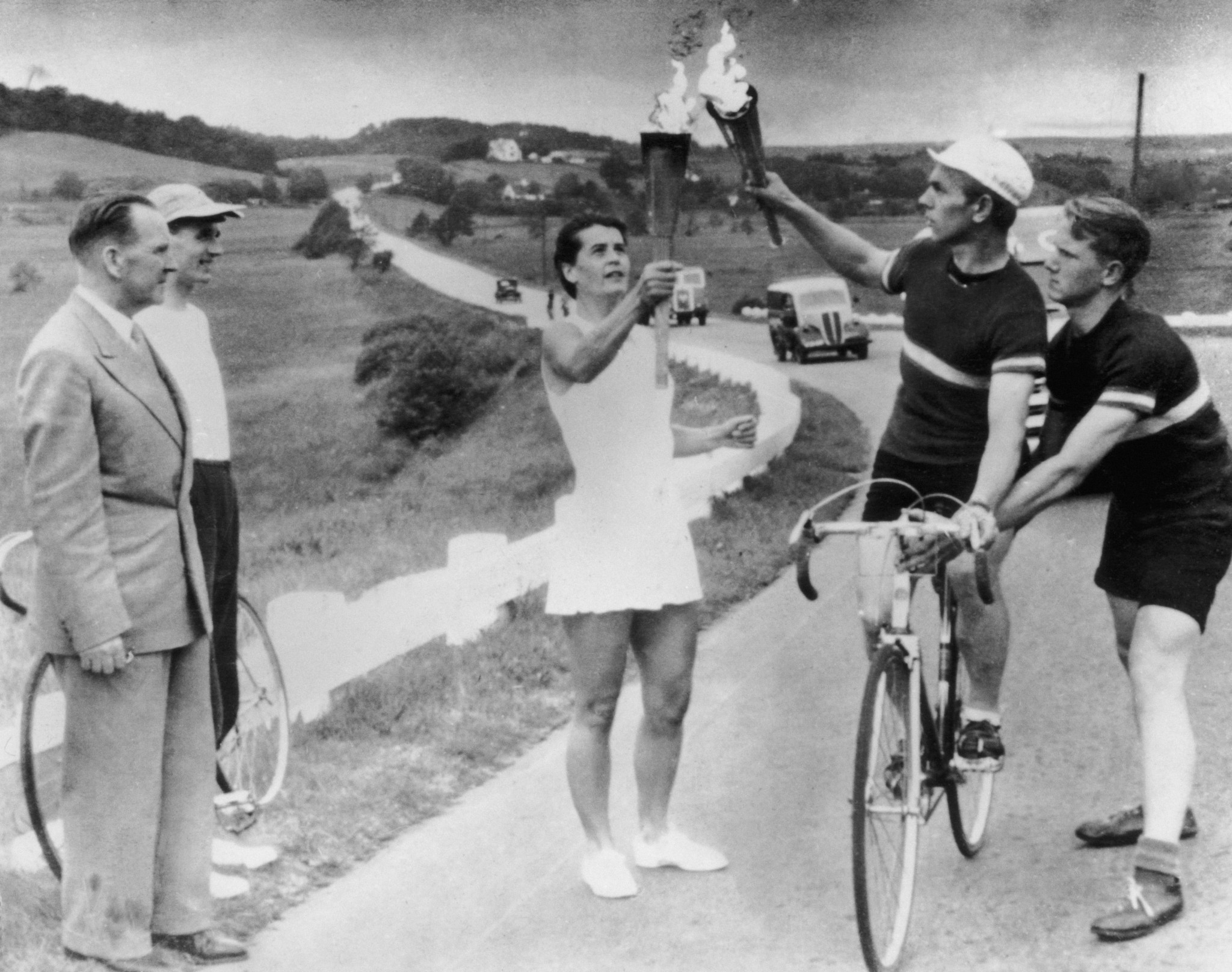 A Relay runner passes the Olympic Flame to a cyclist on the road between Aalborg and Randers in Jutland, before the Helsinki 1952 Games ©Getty Images