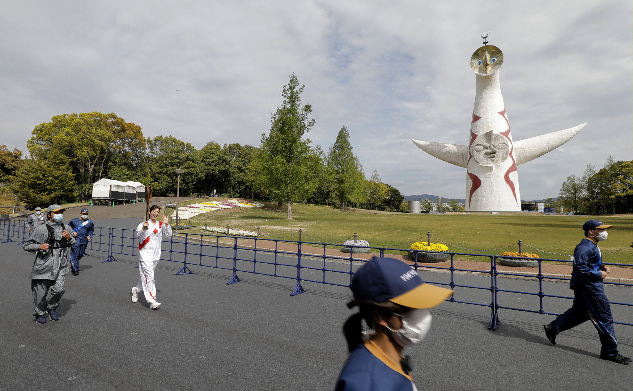 Former Japanese swimmer Aya Terakawa carries the Olympic Flame through a virtually empty Commemorative Park in Osaka ©Getty Images