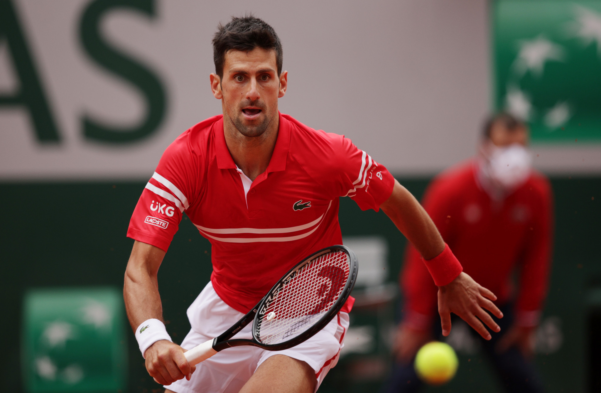 Novak Djokovic chases down the ball as he continues his bid to claim a second French Open title ©Getty Images