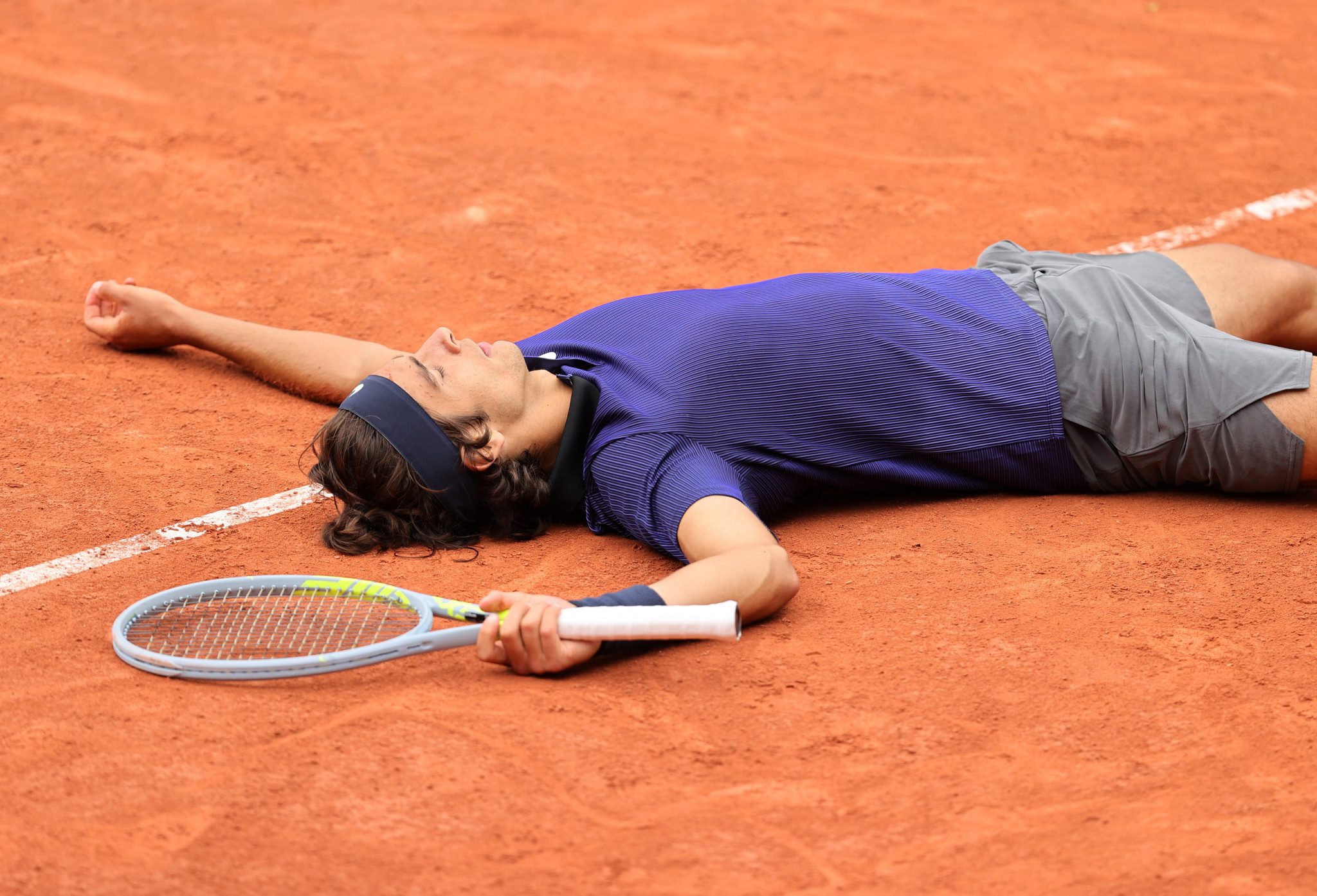 Lorenzo Musetti falls flat on his back after pulling off a five-set win over compatriot Marco Cecchinato ©Getty Images