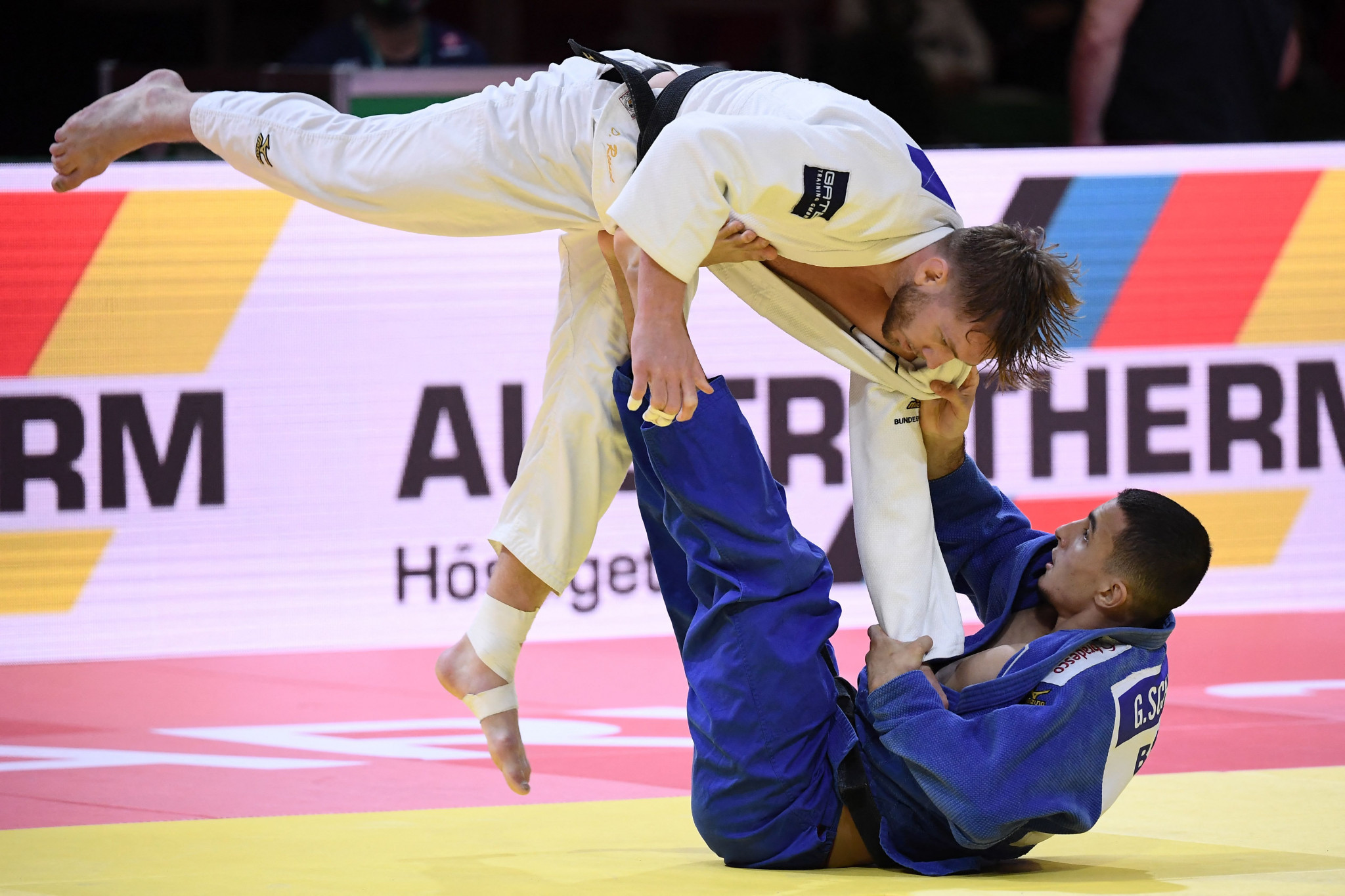 Brazilian Guilherme Schmidt, in blue, lifts Dominic Ressel of Germany off the floor in a closely-fought second-round battle ©Getty Images