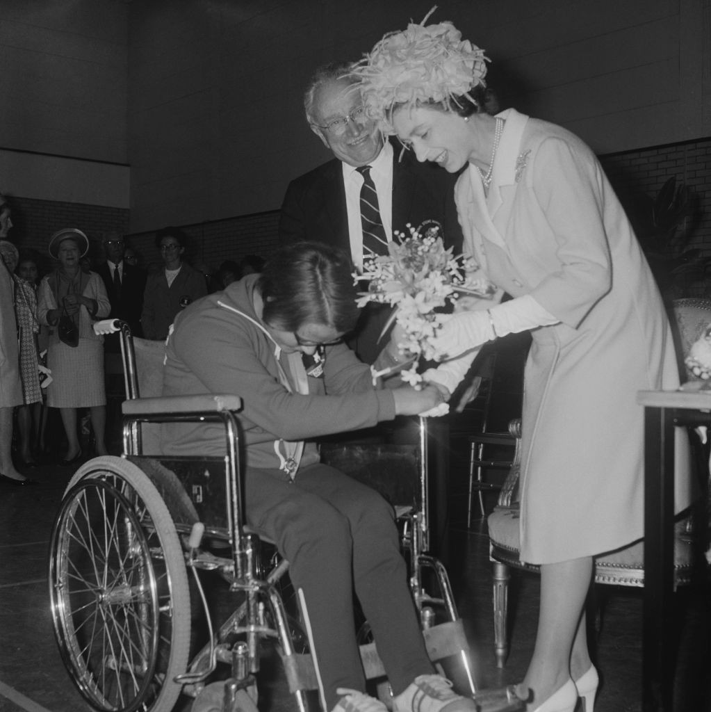 Sir Ludwig Guttmann, founder of the Paralympic Movement, looks on as a competitor at the Stoke Mandeville Games presents a bouquet to the Queen in 1969 ©Getty Images