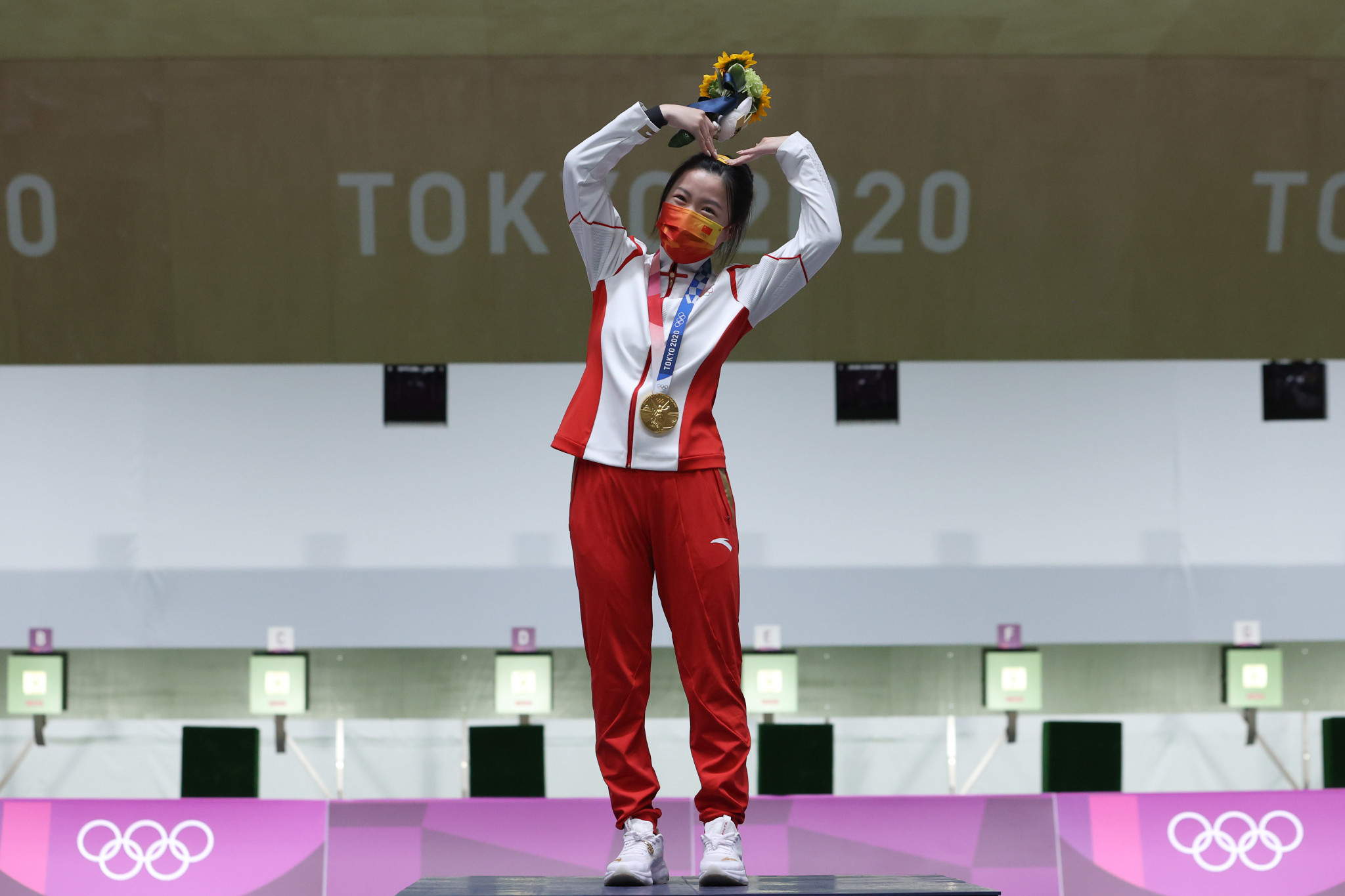 Champion Qian Yang of China poses at the top of the podium during the women's 10-metre air rifle medal ceremony ©Getty Images