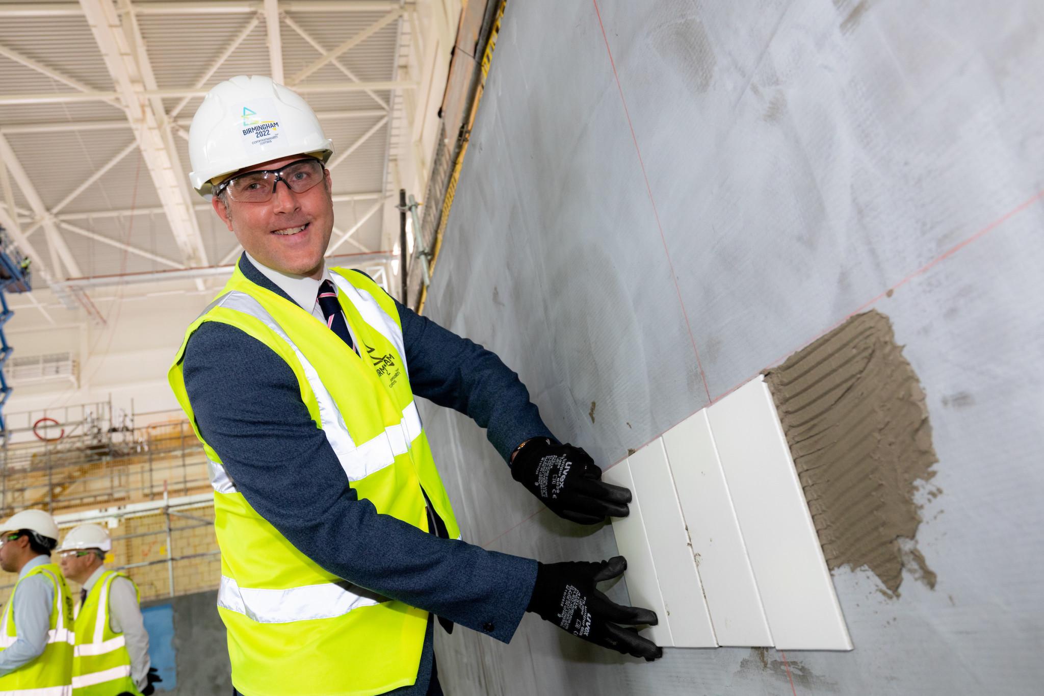 Ian Reid lays the first tiles at the Sandwell Aquatics Centre ©Birmingham 2022