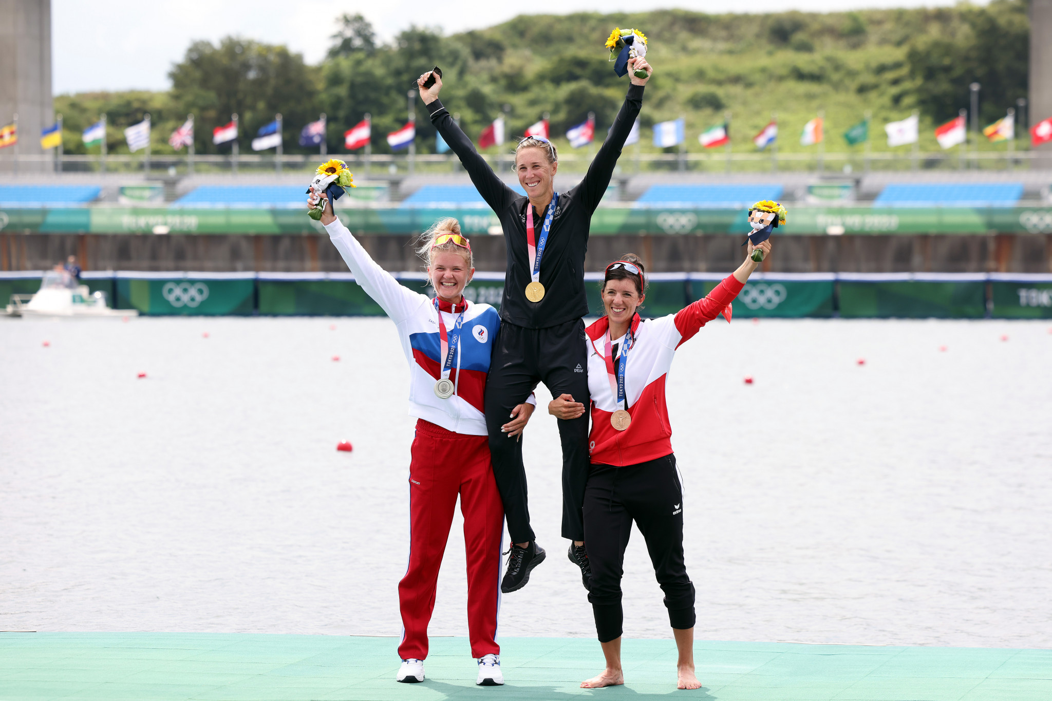 New Zealand's Emma Twigg is held aloft by Russia's Hanna Prakatsen and Austria's Magdalena Lobnig after winning at the fourth time of asking at the Olympics ©Getty Images