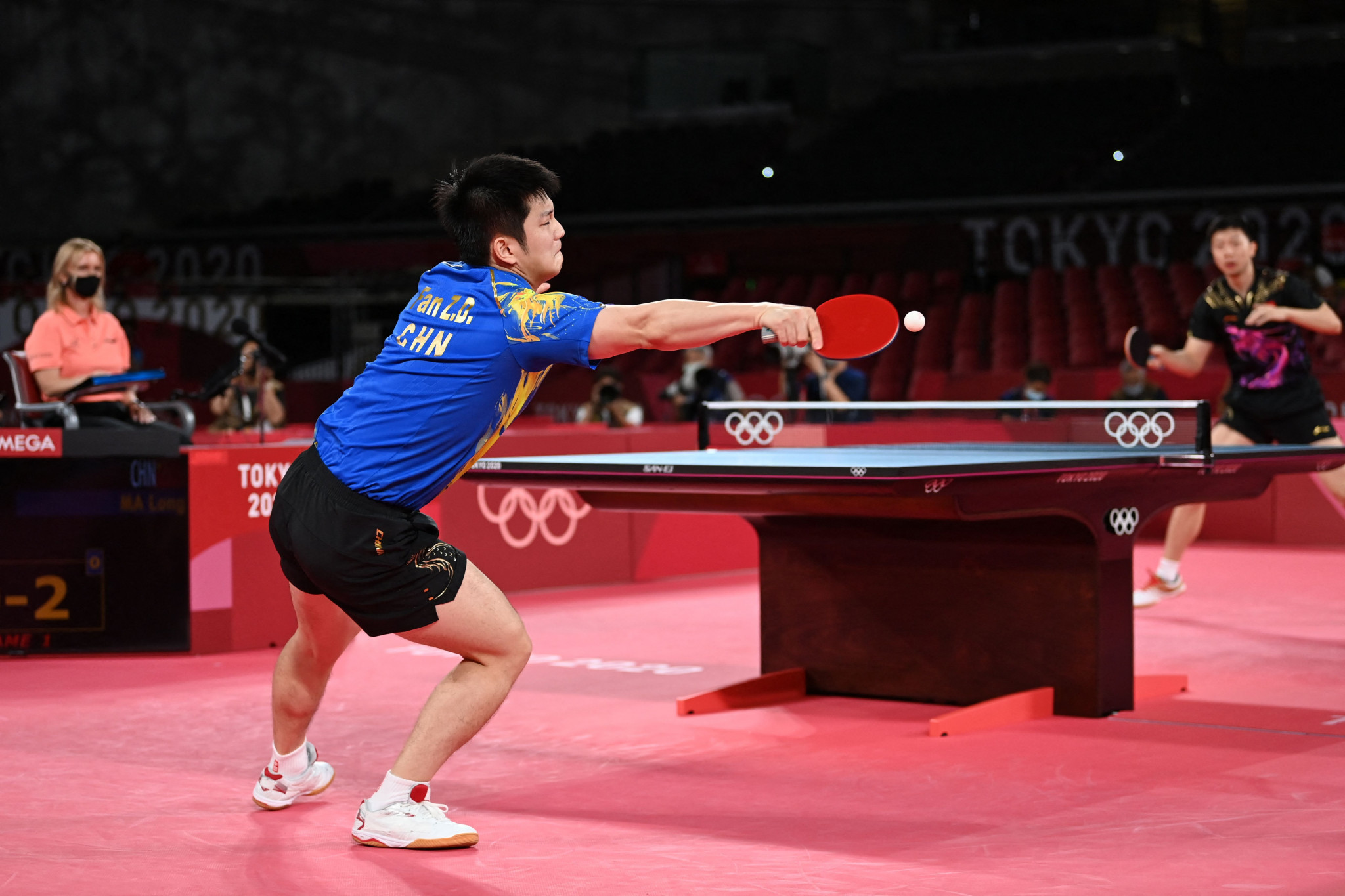 Fan Zhendong stretches to retrieve a shot by Ma Long during their thrilling men's singles final in Tokyo ©Getty Images