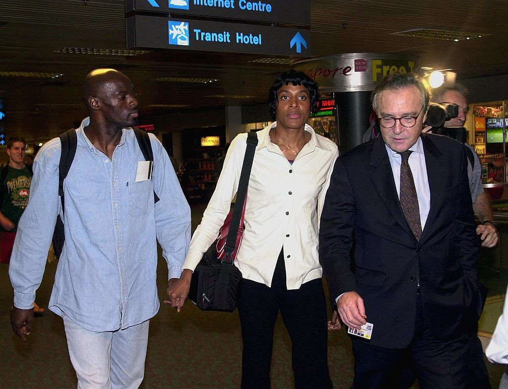 Marie-José Pérec and her boyfriend Anthuan Maybank are accompanied by the French ambassador as they leave Singapore after 11 hours of questioning en route from Sydney to Paris in 2000 ©Getty Images