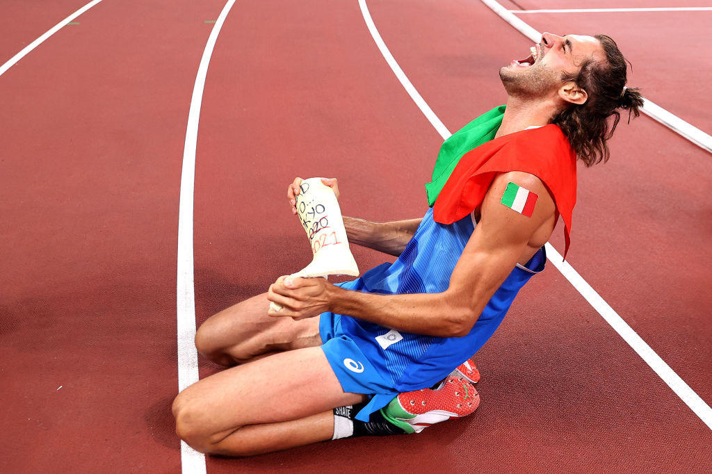 Gianmarco Tamberi, exultant on the track after winning a share of Olympic high jump gold, holds the cast he had put on his leg after a career-threatening injury shortly before Rio 2016 ©Getty Images