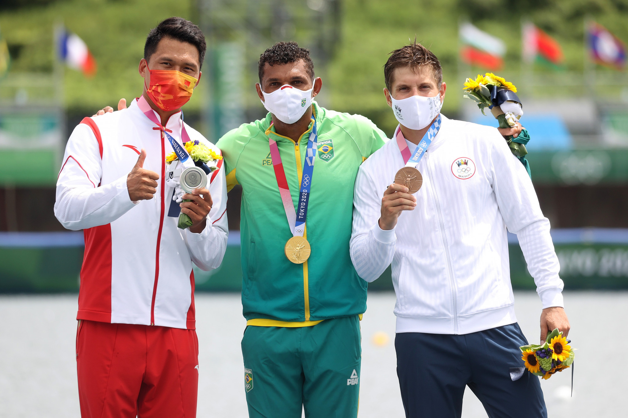 Serghei Tarnovschi, right, who was banned for four years in 2016 due to a positive doping test, stands on the podium alongside champion Isaquias Queiroz and Lui Hao ©Getty Images