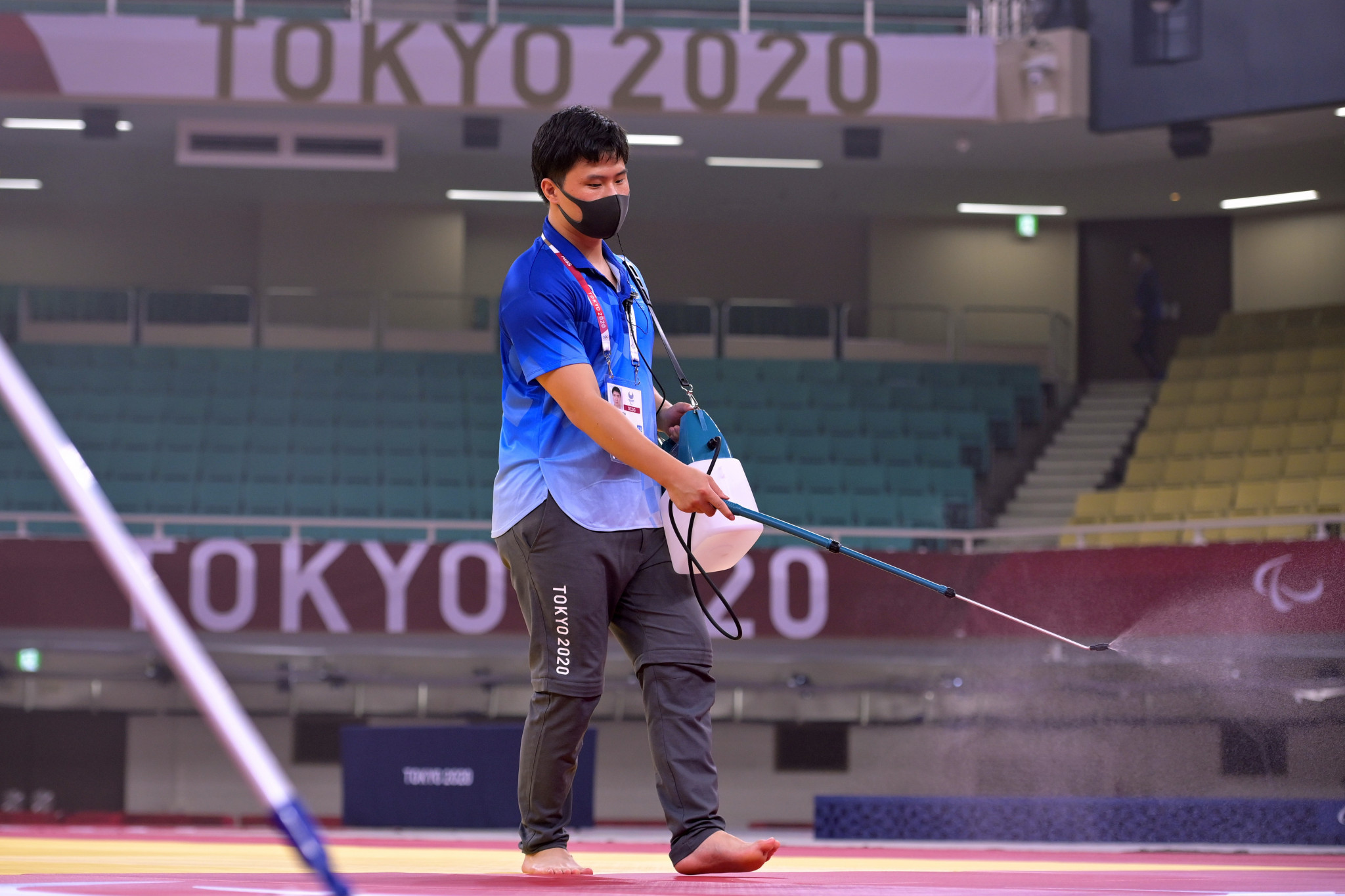 Tokyo 2020 staff spray the mats at the Nippon Budokan as part of the organisation's COVID-19 cleaning protocols ©Getty Images