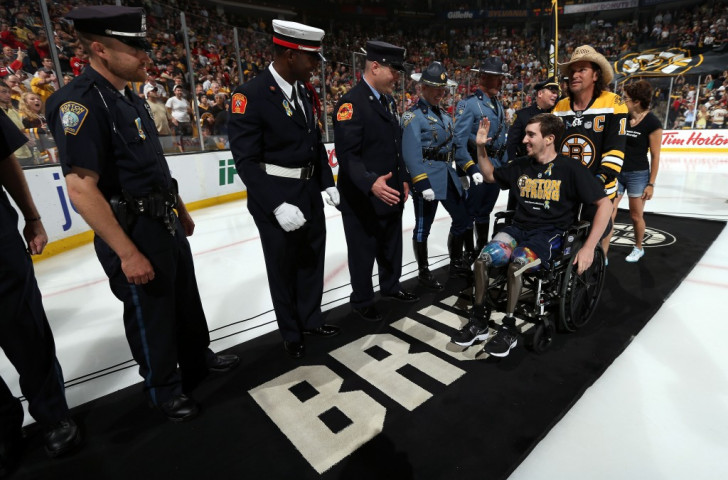 Jeff Bauman, who lost both legs in the Boston Marathon bombings, is wheeled onto the ice before the Boston Bruins' NHL Stanley Cup final game six in June 2013 ©Getty Images