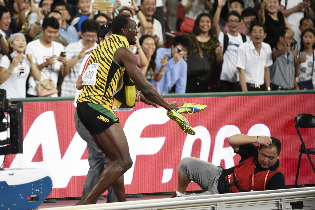 Usain Bolt reacts after being knocked down from behnd by a mobile cameraman who lost control of his Segway machine ©Getty Images